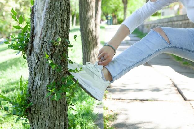 La fille redresse les lacets des chaussures dans le parc