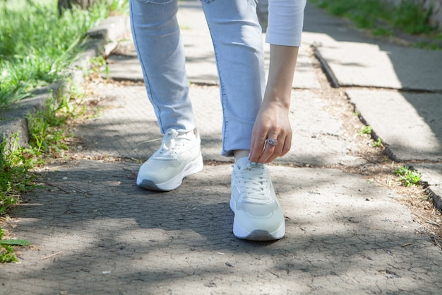 La fille redresse les lacets de ses chaussures dans la rue