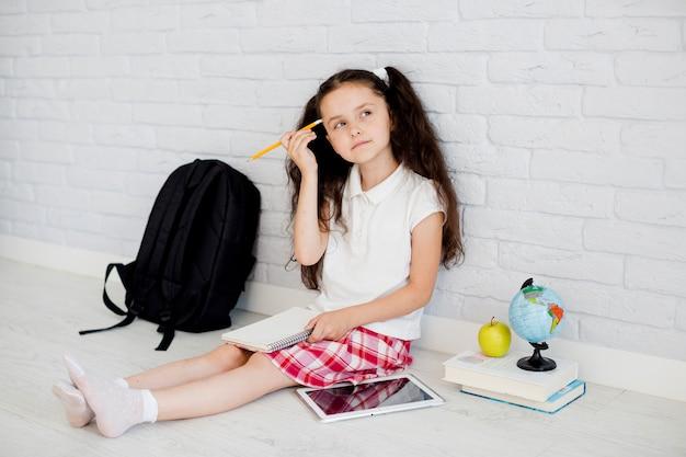 Une fille réfléchie avec un bloc-notes