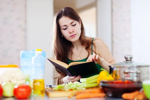 Fille réfléchie cuisine avec livre de cuisine