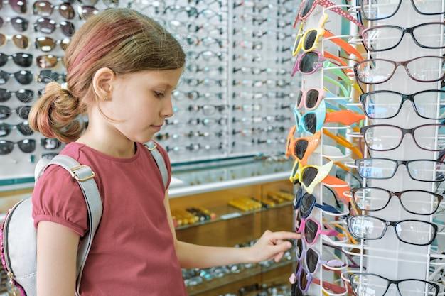 Fille regardant et choisissant des lunettes de soleil