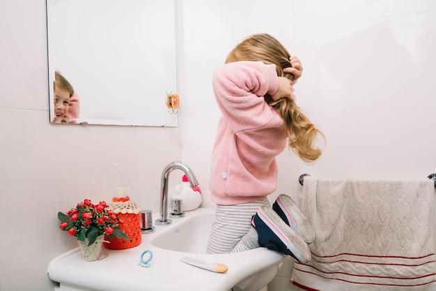 Fille regardant dans le miroir attachant ses cheveux