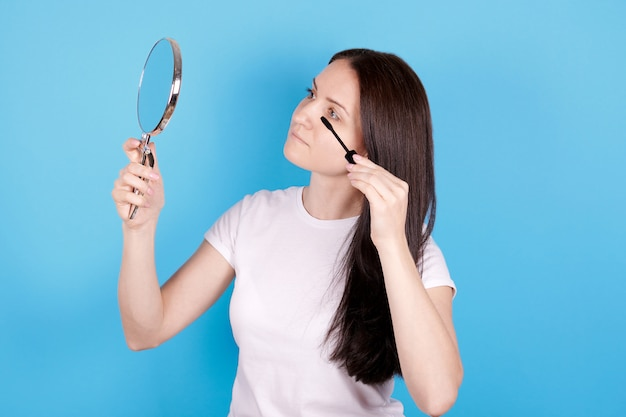 Fille regardant miroir et utilisant maskara. isolé sur fond bleu.