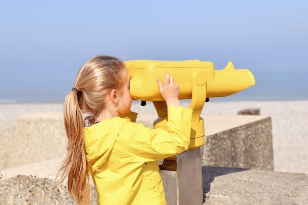 Une fille regardant l'océan à travers un binoscope