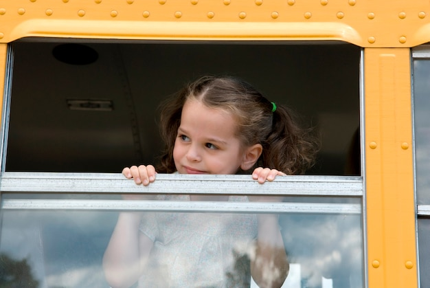 Fille regardant par la fenêtre