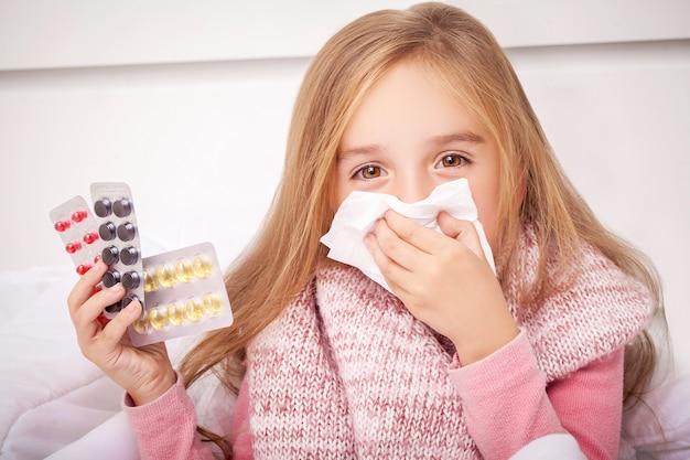 Fille regardant les pilules contre le rhume et la grippe