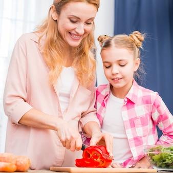 Fille regardant sa mère couper les poivrons rouges avec un couteau sur une planche à découper