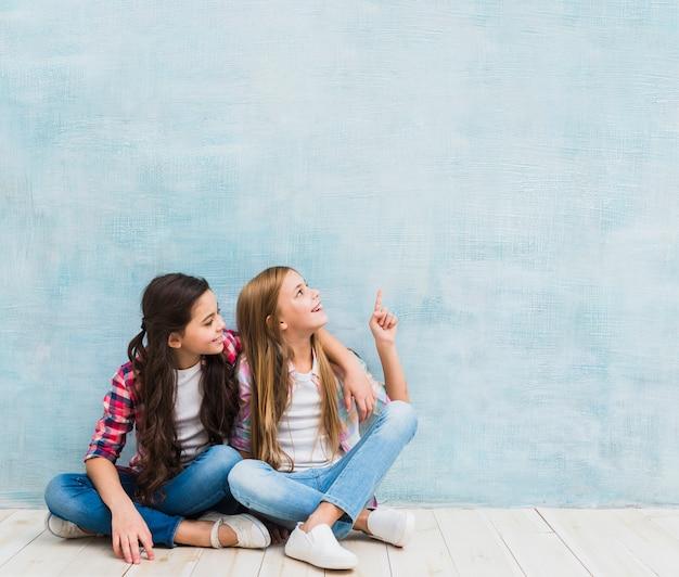 Fille regardant son ami souriant, pointant le doigt vers le haut sur fond bleu