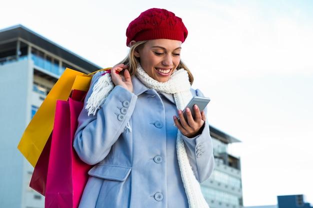 Fille regardant son téléphone pendant les achats à l'extérieur