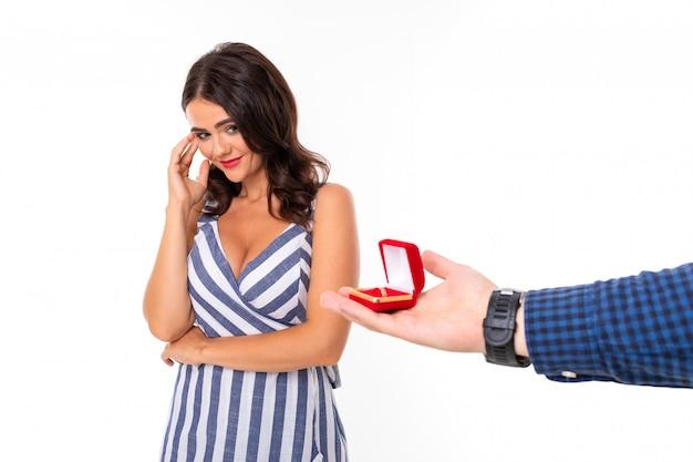 Fille regarde un anneau dans une boîte par laquelle un homme fait une demande en mariage sur un mur blanc