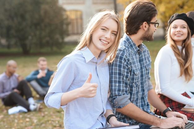 La fille regarde la caméra, assise avec des amis.