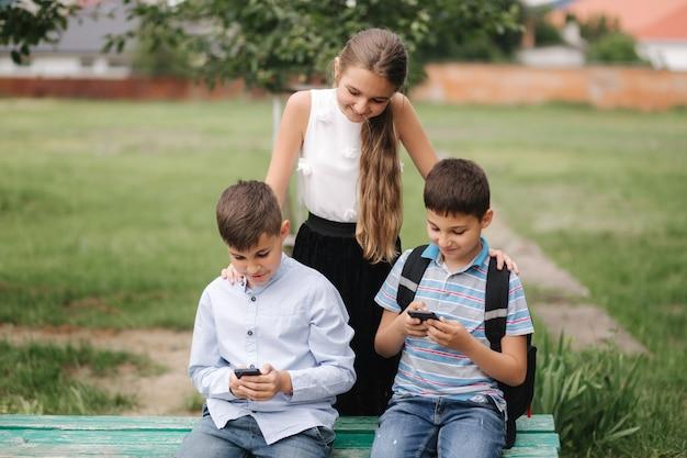 Fille regarde comment le garçon joue au jeu en ligne. deux garçons jouent à des jeux en ligne en quarantaine. les jeunes garçons sourient et