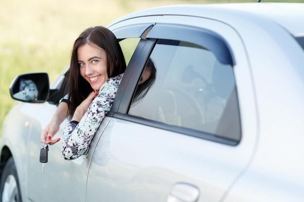Fille regarde par la fenêtre tenant les clés de voiture en main