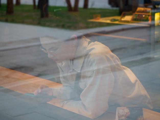 La fille regarde le téléphone dans le café, dans la fenêtre. dans la vitrine d'un café ou d'une boutique, la rue de la ville se reflète. le concept de prévenance, d'attente.