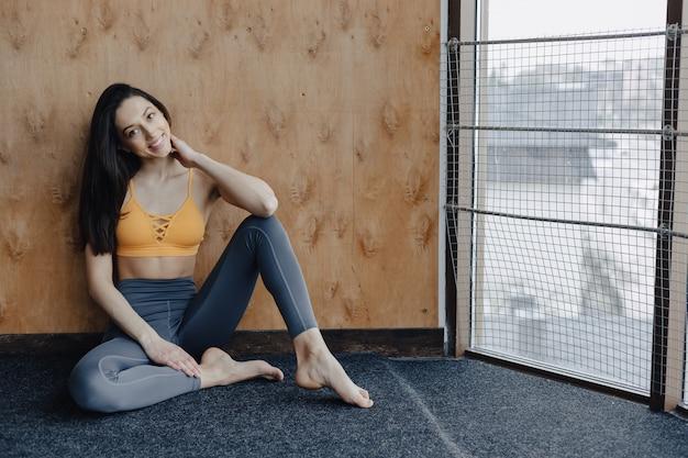 Fille de remise en forme attrayante jeune assis sur le sol près de la fenêtre