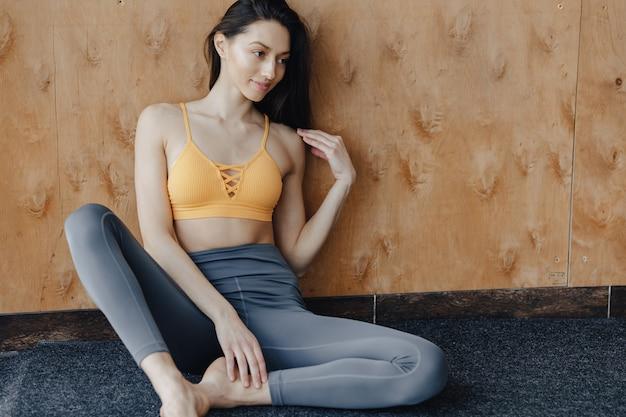 Fille de remise en forme attrayante jeune assis sur le sol, reposant sur des cours de yoga