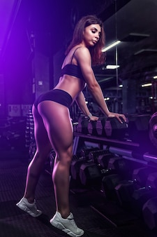 Fille de remise en forme exerçant et posant avec haltères dans la salle de gym.