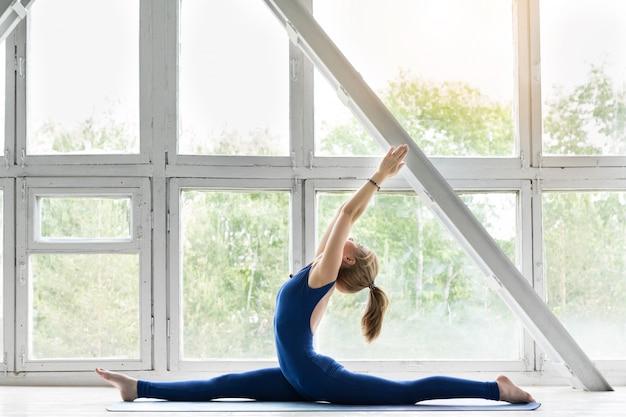 Fille de remise en forme faisant du yoga asana en classe