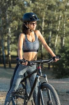 Une fille de remise en forme fait du vélo de montagne moderne en fibre de carbone en tenue de sport.