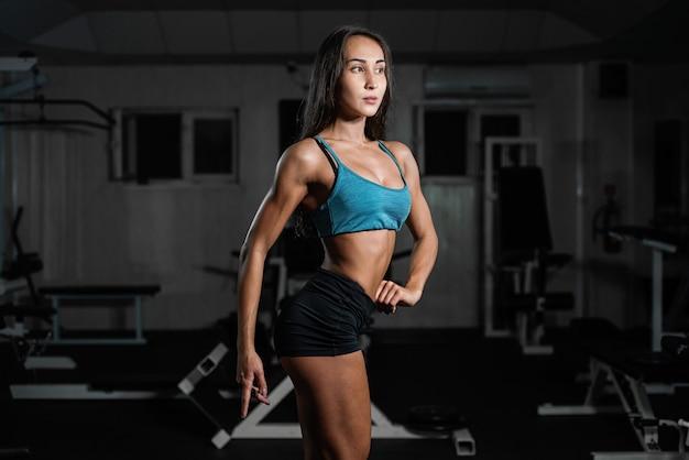 Fille de remise en forme avec haltère, femme posant dans une salle de sport