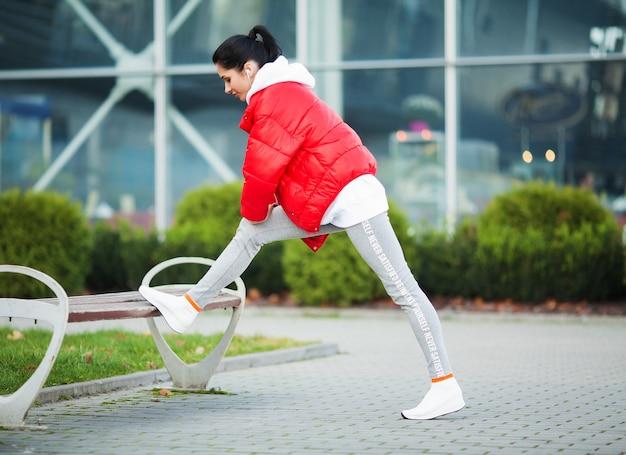 Fille de remise en forme. jeune femme sportive qui s'étend dans la ville moderne. mode de vie sain dans la grande ville