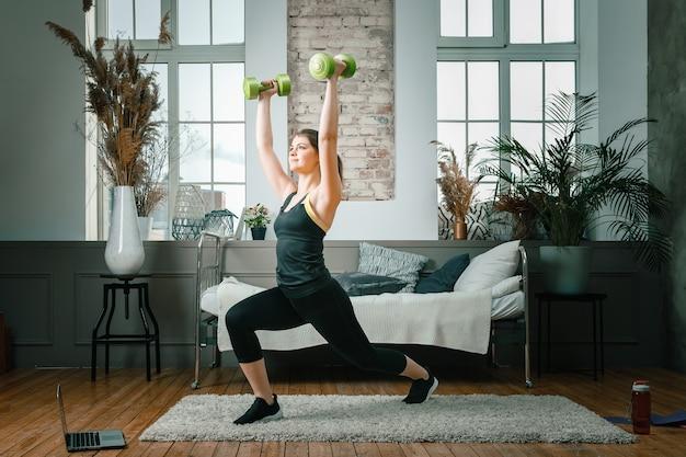 Une fille de remise en forme sportive forte et belle en tenue de sport se fend avec des haltères