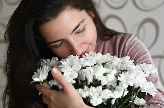 Fille renifle un bouquet de fleurs blanches. brunette embrasse renifle un bouquet de fleurs délicates de sa bien-aimée. un joli cadeau pour votre moitié bien-aimée.