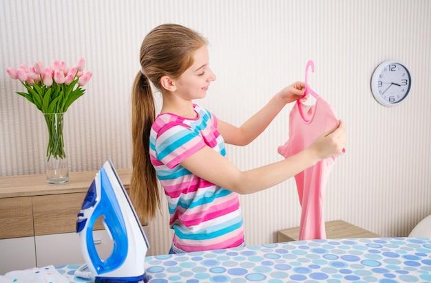 Fille de repasser les vêtements à bord à la maison
