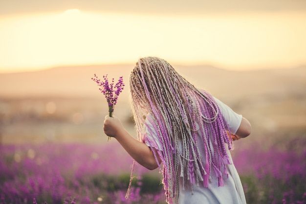 Fille représentée de dos avec un bouquet dans un champ de lavande