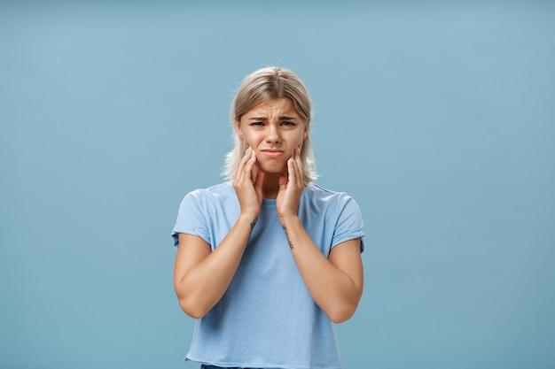 Fille ressentant de la douleur dans les dents après avoir bu du café chaud. mécontent malheureux jeune fille aux cheveux blonds fronçant les sourcils sentiment d'inconfort dans la bouche se tenant la main sur les joues souffrant de maux de dents