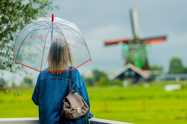 Fille rester sur le pont avec des moulins néerlandais
