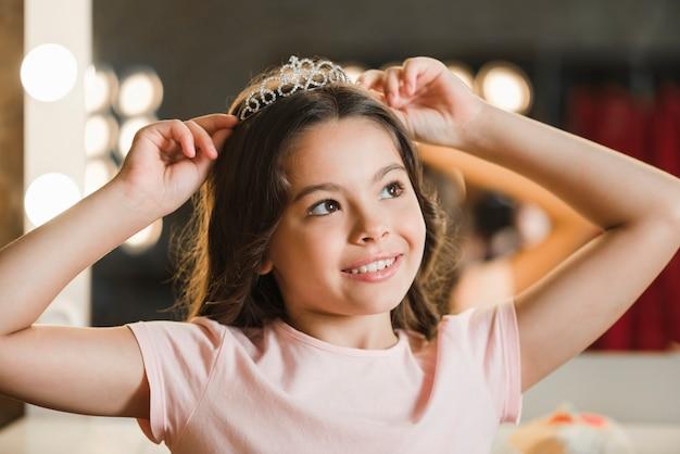 Fille rêvant tenant la couronne sur la tête en détournant les yeux