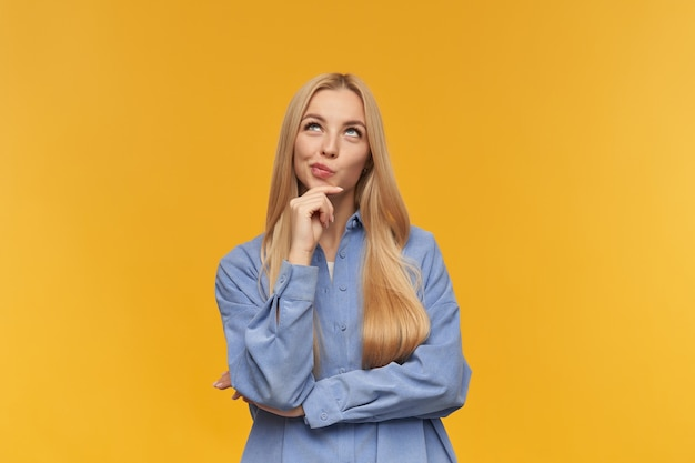 Fille de rêve, femme à la recherche heureuse aux cheveux longs blonds. porter une chemise bleue. concept de personnes et d'émotion. toucher son menton et pincer les lèvres. watching up at copy space, isolé sur fond orange