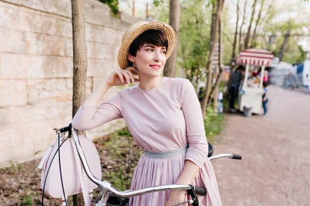 Fille de rêve en tenue élégante posant pendant un voyage à vélo debout près du mur de pierre dans la rue