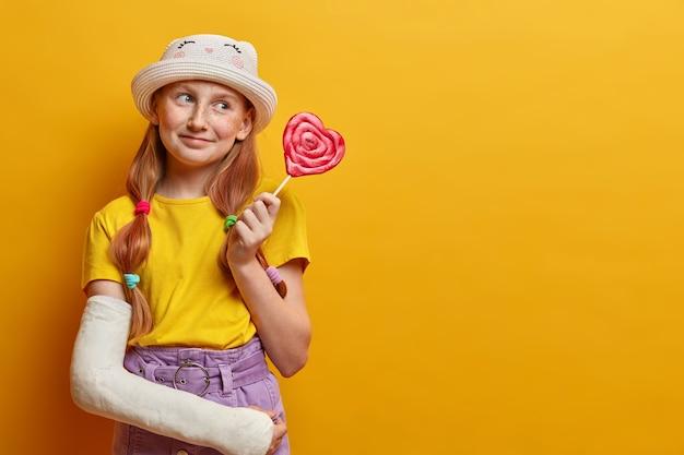 Une fille rêveuse aux taches de rousseur positives pose avec une grosse sucette en forme de coeur, a la dent sucrée, aime manger des aliments nocifs, tient de délicieux bonbons, porte une tenue d'été à la mode, a un bras cassé. dépendance au sucre
