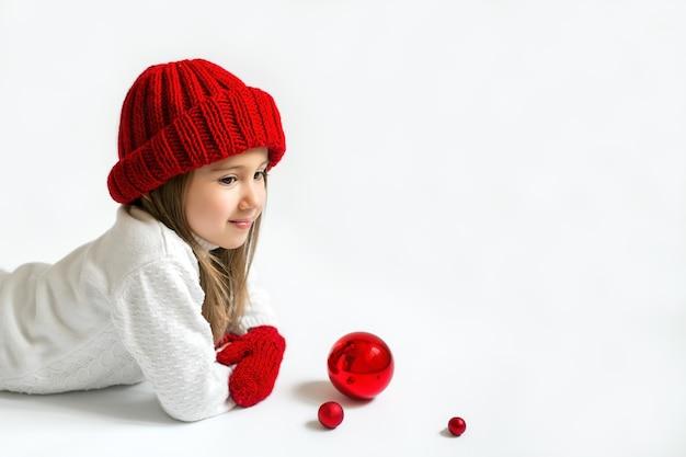 Fille rêveuse dans un chapeau d'hiver rouge tricoté avec des boules de noël sur fond blanc