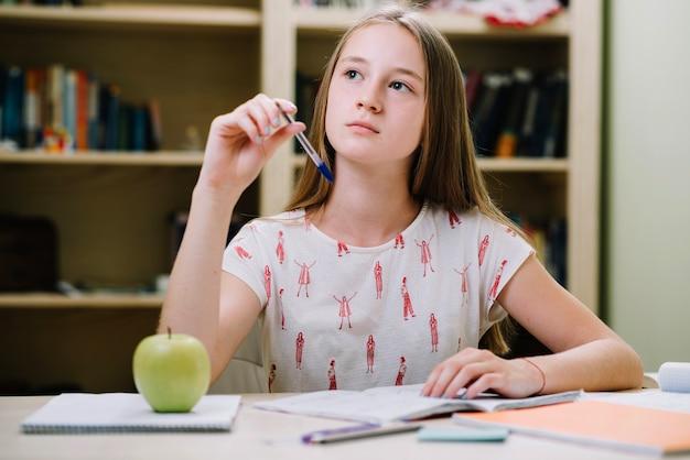 Une fille rêveuse qui étudie