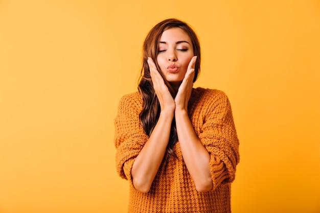 Fille rêveuse en vêtements tricotés touchant son visage. femme brune inspirée avec un maquillage léger debout sur le jaune.