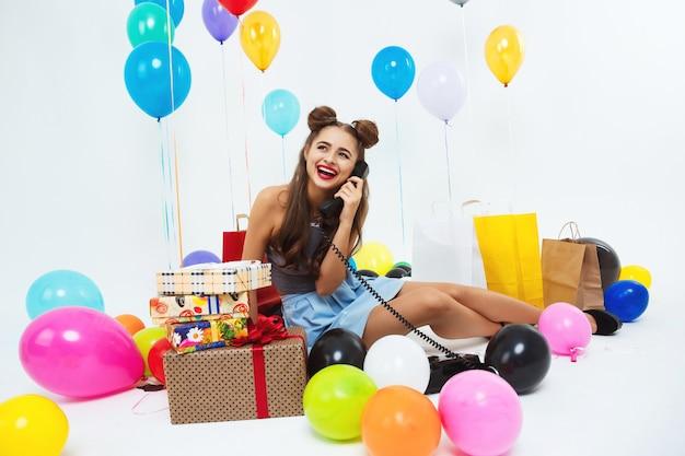 Fille riante après une grande fête d'anniversaire, parler au téléphone