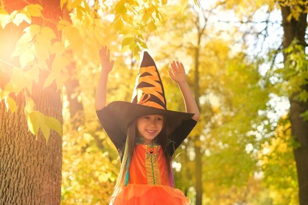 Une fille riante heureuse dans un chapeau et une robe de sorcière avec ses mains vers le haut
