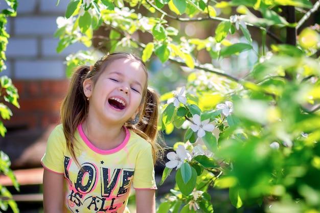 La fille rit debout près de l'arbre en fleurs