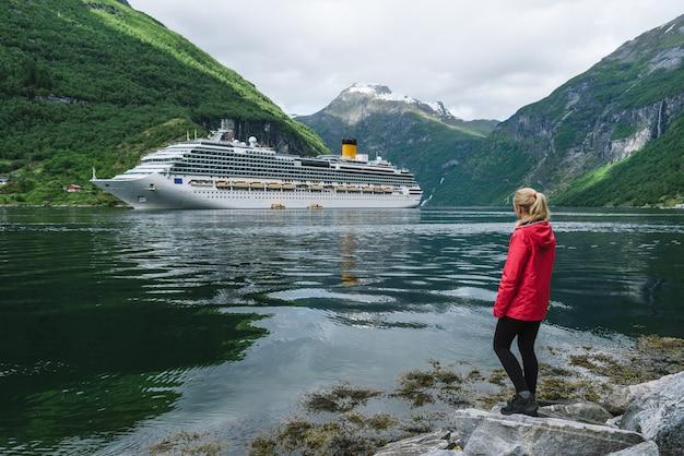 Fille sur la rive du fjord de geiranger