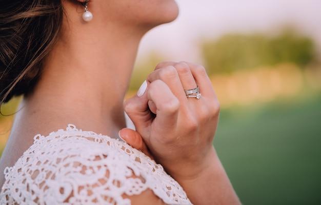 Fille en robe blanche et avec des boucles d'oreilles blanches, tenant les mains près du cou