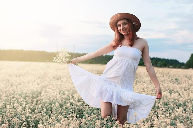 Fille en robe blanche dans le champ de fleurs jaunes en fleurs