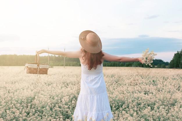 Fille en robe blanche dans le domaine de la floraison des fleurs jaunes