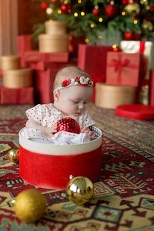 Une fille en robe blanche à pois rouges est assise dans une boîte-cadeau avec une boule de noël dans les mains