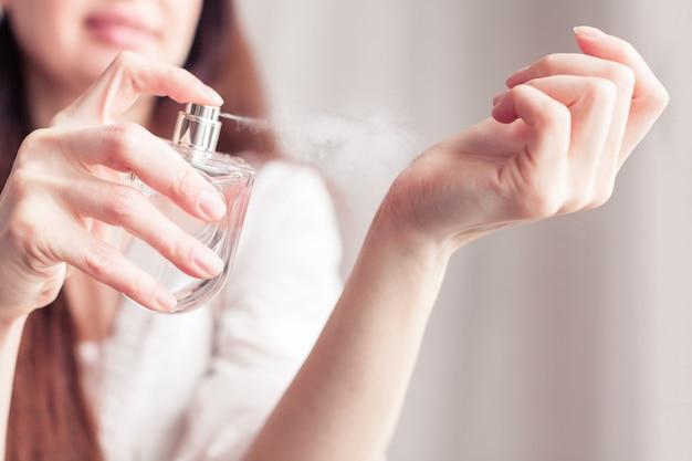Une fille en robe blanche se vaporise du parfum sur son poignet