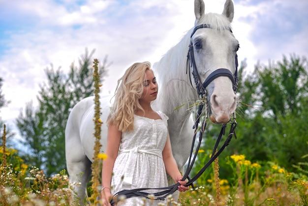 Fille en robe blanche tenant un cheval dans le champ