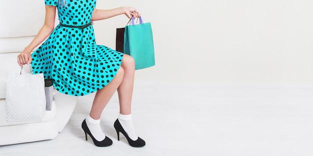 Fille en robe bleue et chaussures noires avec des sacs à provisions sur fond blanc. vendredi noir