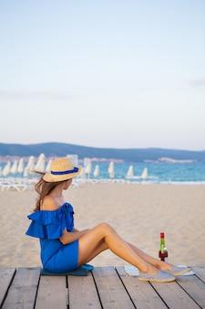 Fille en robe bleue est assise sur une plage de sable